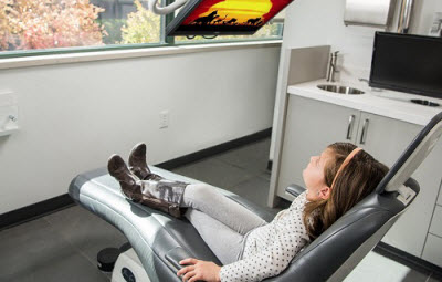 little girl in dental chair relaxing while watching movie on TV in Studio Z Dental