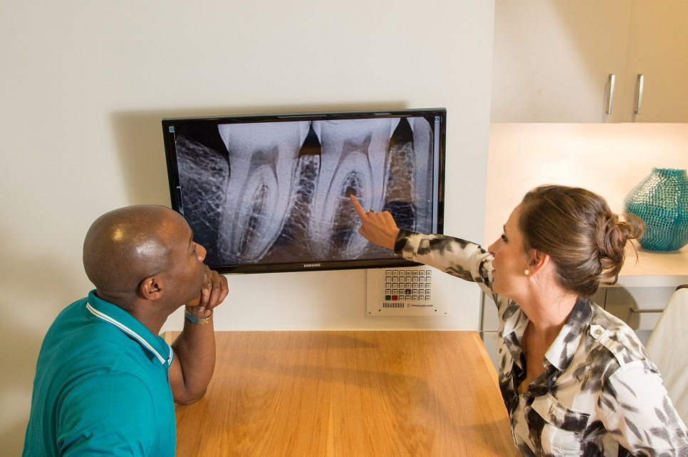 Patient and team member reviewing dental x-rays in office.