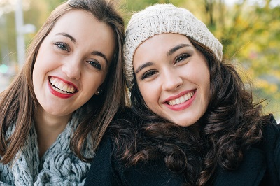 Laughing best friends posing for a selfie outdoors in autumn