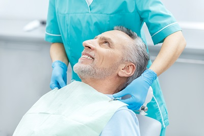 Cropped shot of smiling mature patient getting treatment in dental office