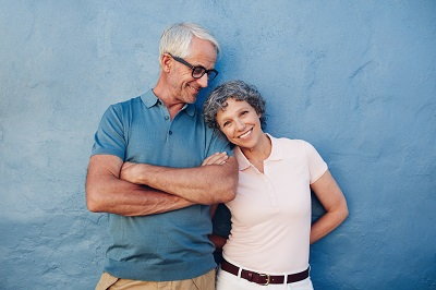Portrait of beautiful mature woman standing with her husband against blue background.