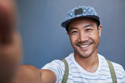 ortrait of a stylishly dressed young Asian man smiling and taking a selfie while standing alone in front of a gray wall outside