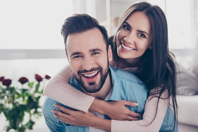 Close up photo of cheerful couple at home. woman hugging man from the back