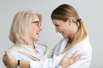 Happy senior mother embracing adult daughter laughing together