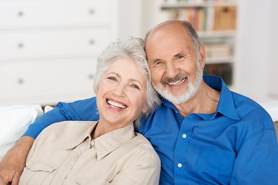 Romantic senior couple sitting close together on a sofa in the house smiling happily at the camera