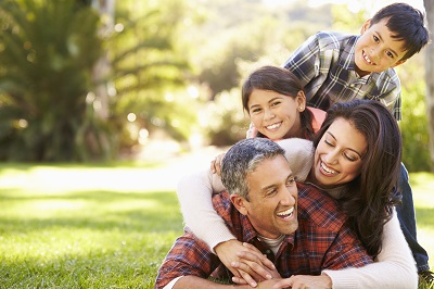 Hispanic Family Lying On Grass In Countryside