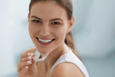 blonde woman holding invisalign clear aligners