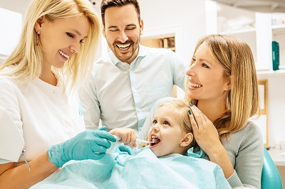 little girl learning how to brush properly in dental office with parents in background