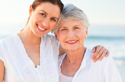 senior woman and adult daughter smiling