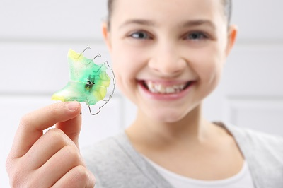 young girl holding metal retainers