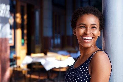 Side portrait of smiling young african american woman standing outside