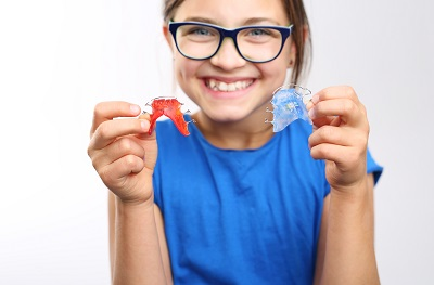 young girl holding orthodontic retainers
