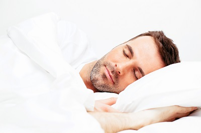 Handsome young man sleeping in white bedding