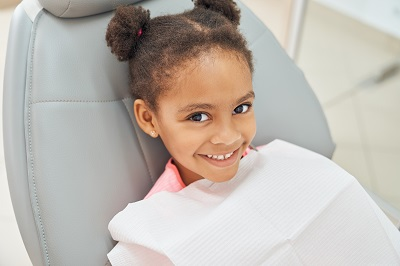 Charming little afro american girl sitting in dental chair smiling and looking at camera