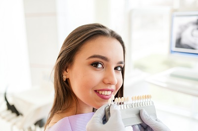 Beautiful girl in dentist office matching her teeth color