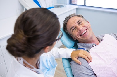 happy patient sitting on dental chair