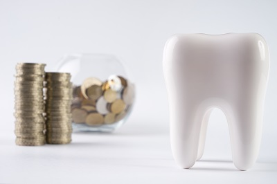 Tooth and piggy box with coins on isolate white background