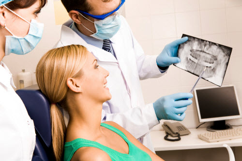 Picture of dentist and hygienist showing a patient a dental x-ray
