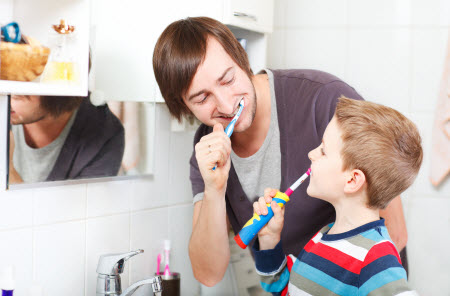 Picture of a father and son brushing their teeth