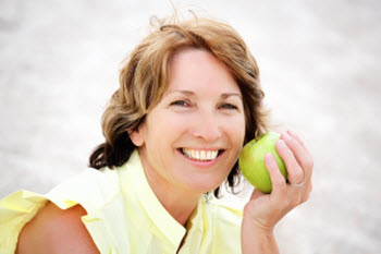 Picture of a woman with dental implants from Alpine Dental Center holding an apple and smiling
