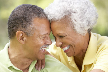Picture of a smiling couple with implant dentures