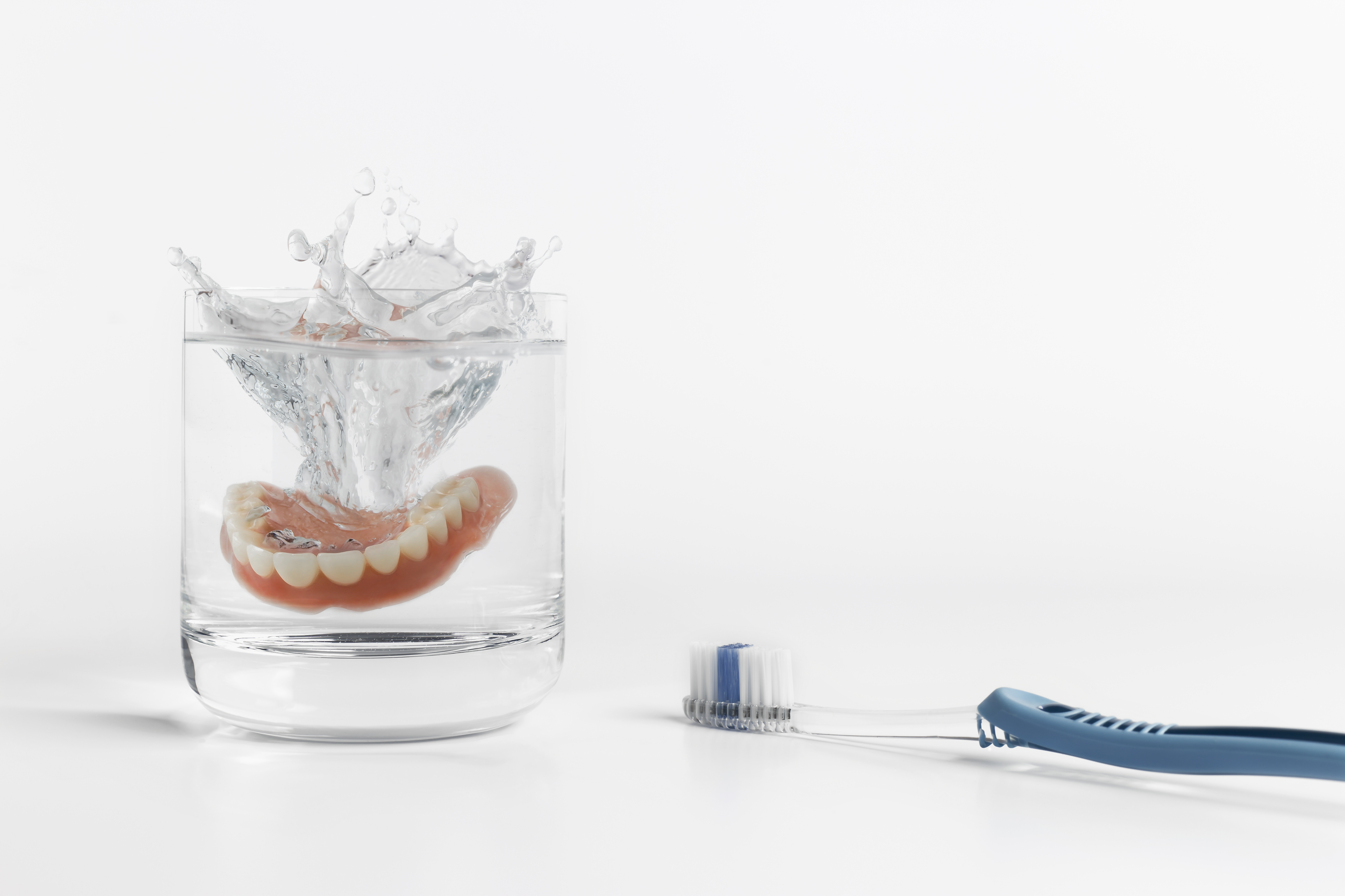 Dentures in cup of water next to toothbrush