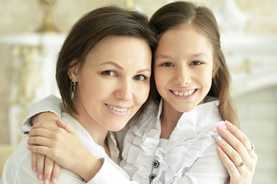 Close up portrait of beautiful young mother and cute little daughter posing