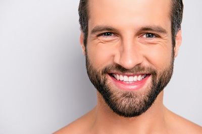 close up of smiling man with beard isolated in white background
