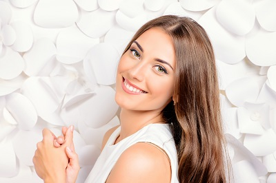 young smiling woman isolated in white background with white flower petals