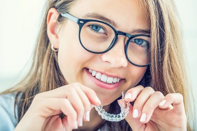 teen girl holding invisalign clear braces