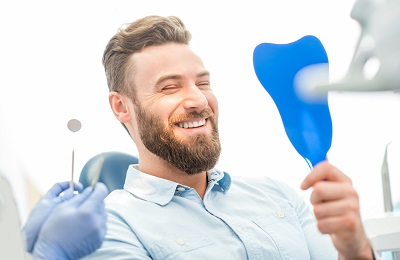 Image of male patient looking at his beautiful smile sitting at the dental office